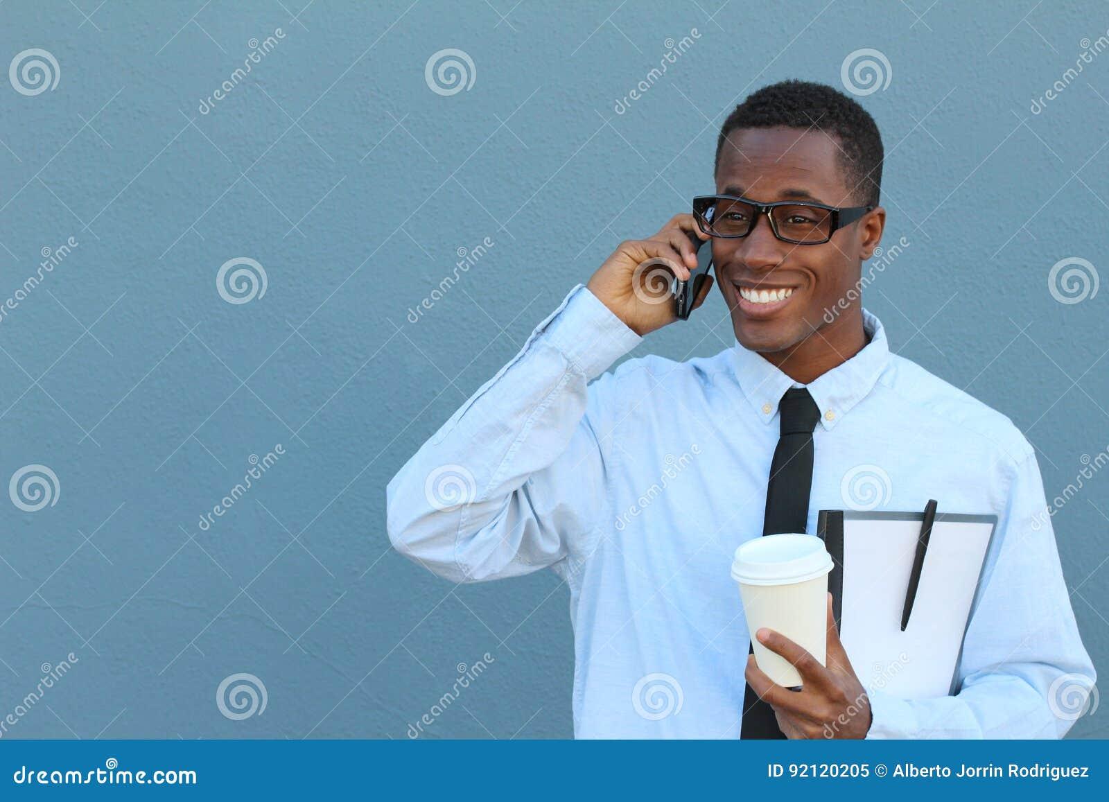 Stående av en kall ung afrikansk man i dräkt och bandet som går och talar på mobiltelefonen