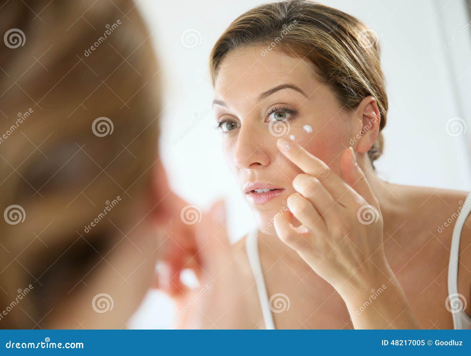 Stående av en kvinna i spegeln som applicerar en kräm
