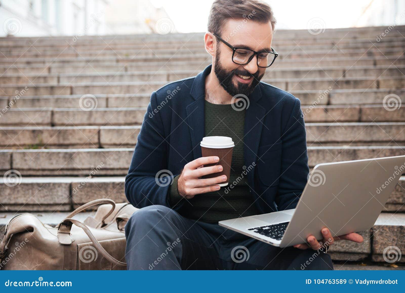 Stående av en le stilig man i glasögon