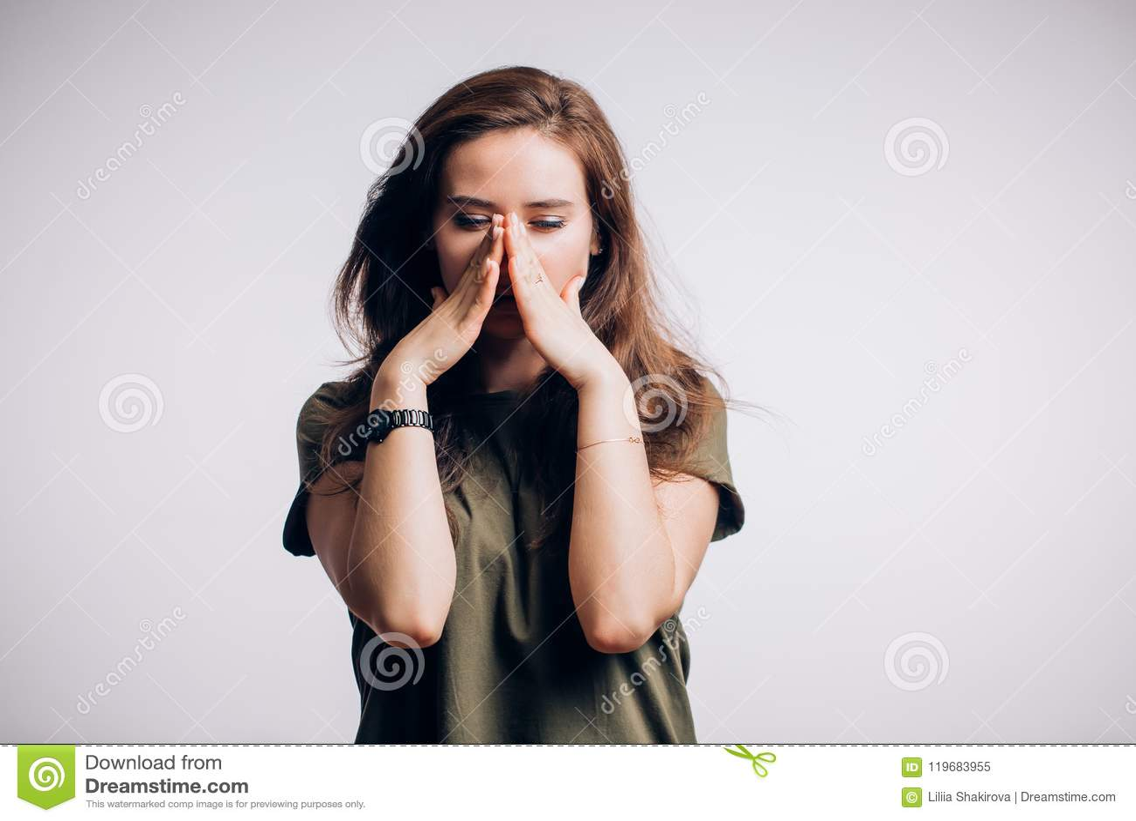 Stående av en ledsen kvinna på en vit bakgrund Bekymrad kvinna som ner ser
