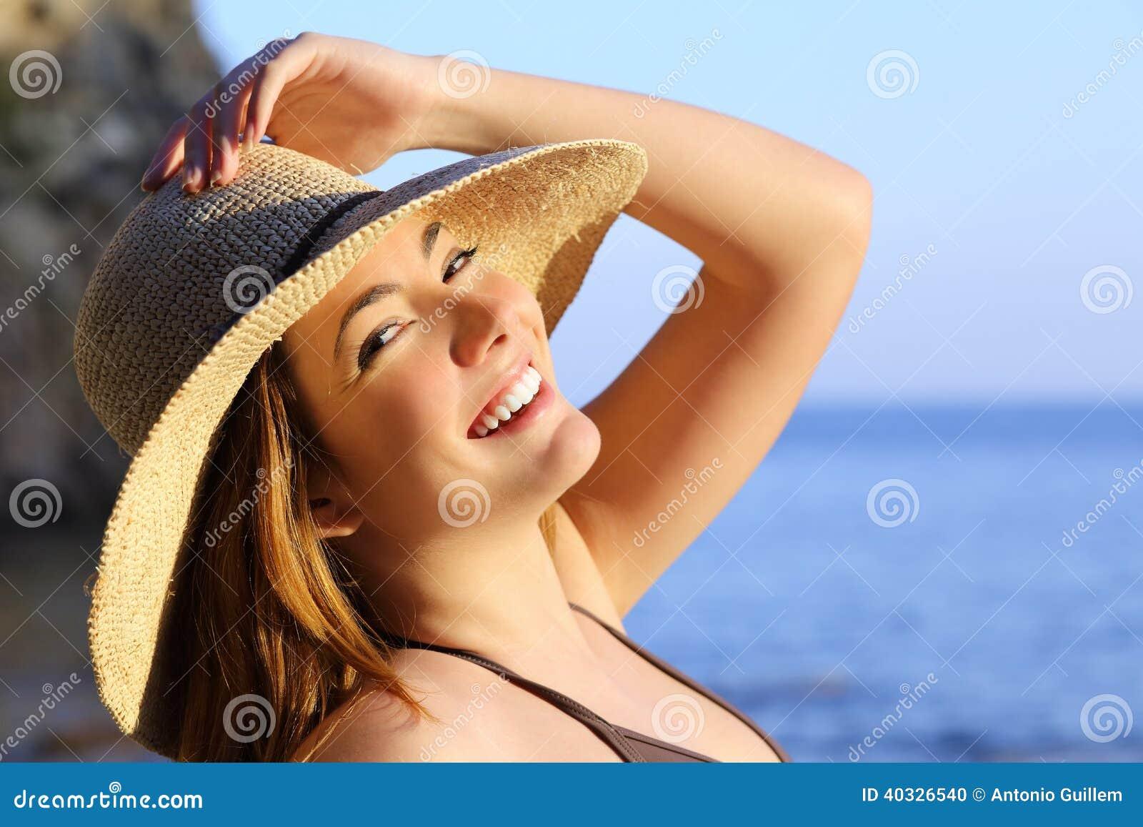 Stående av en lycklig kvinna med perfekt vitt leende på stranden
