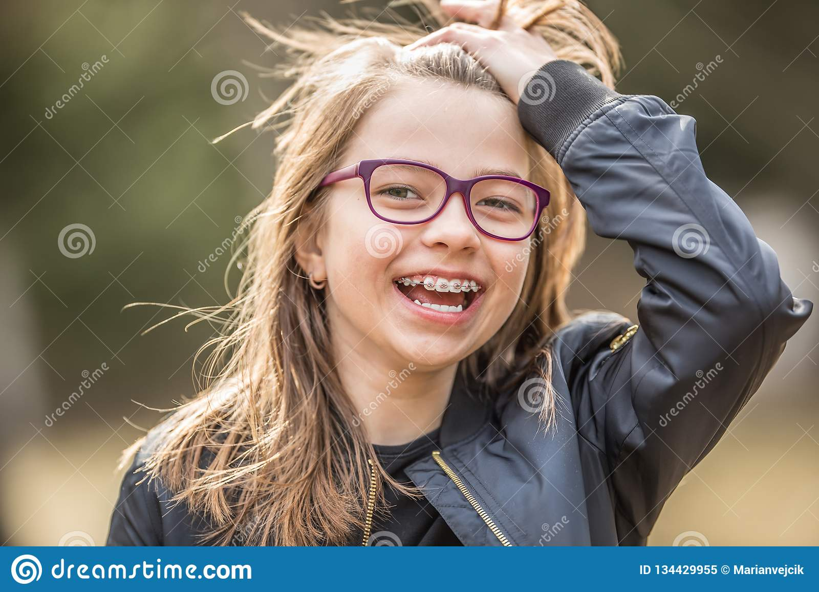 Stående av en lycklig le tonårs- flicka med tand- hänglsen och exponeringsglas