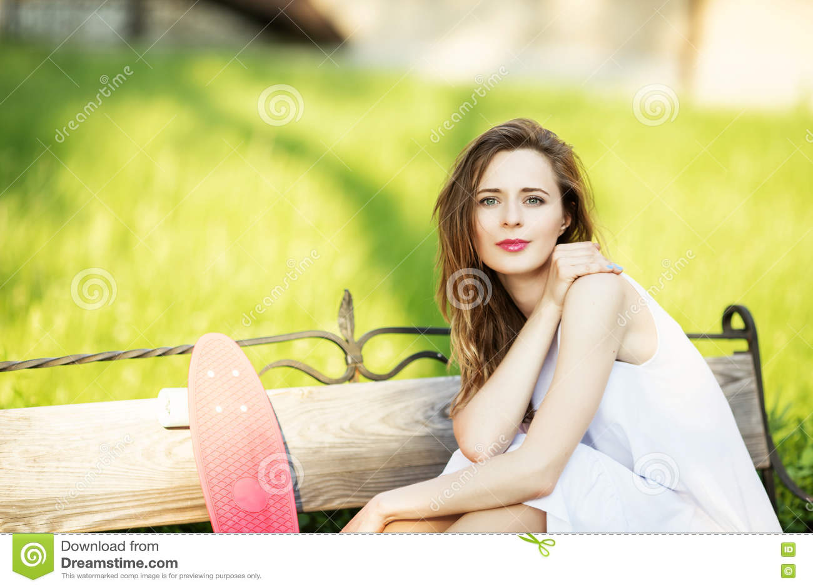 Stående av en lycklig le ung kvinna med en rosa skateboard