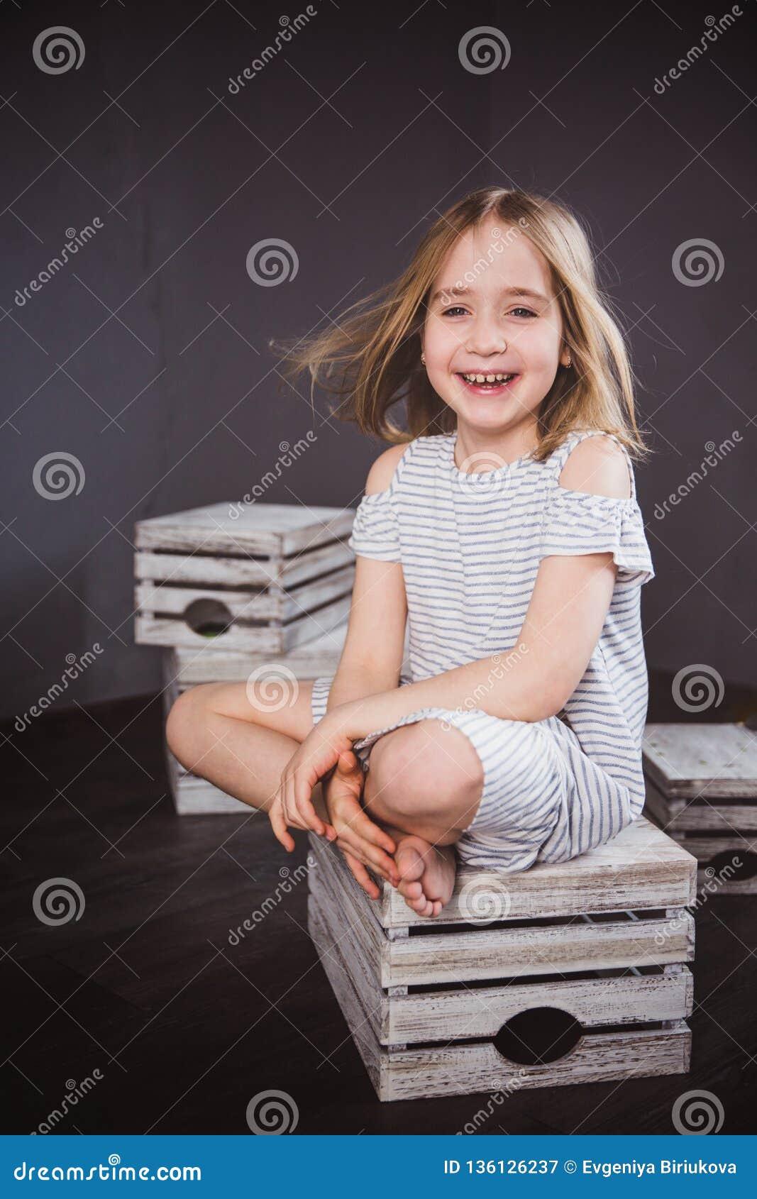 Stående av en lycklig tonårig flicka i sommarklänning i studio Hon sitter på askarna, vinden som blåser hennes hår