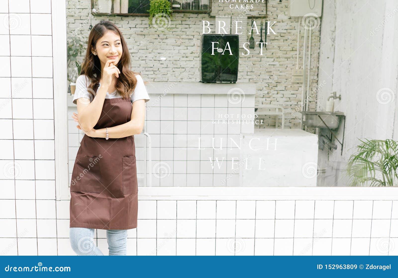 Stående av en lycklig ung asiatisk barista i förklädet som bort ser och framme tänker av hennes lilla coffee shop, midja upp, kop
