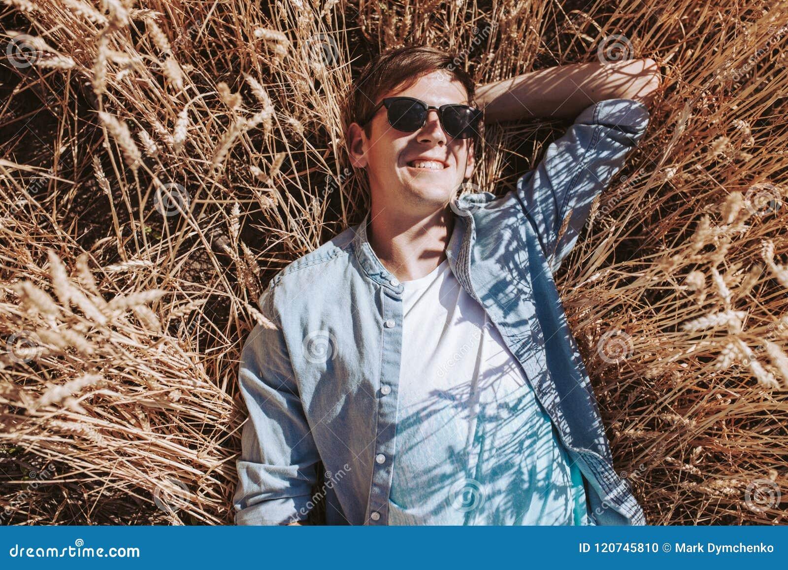 Stående av en man i ett vetefält, en grabb med exponeringsglas och ett lock, i stilen av mode