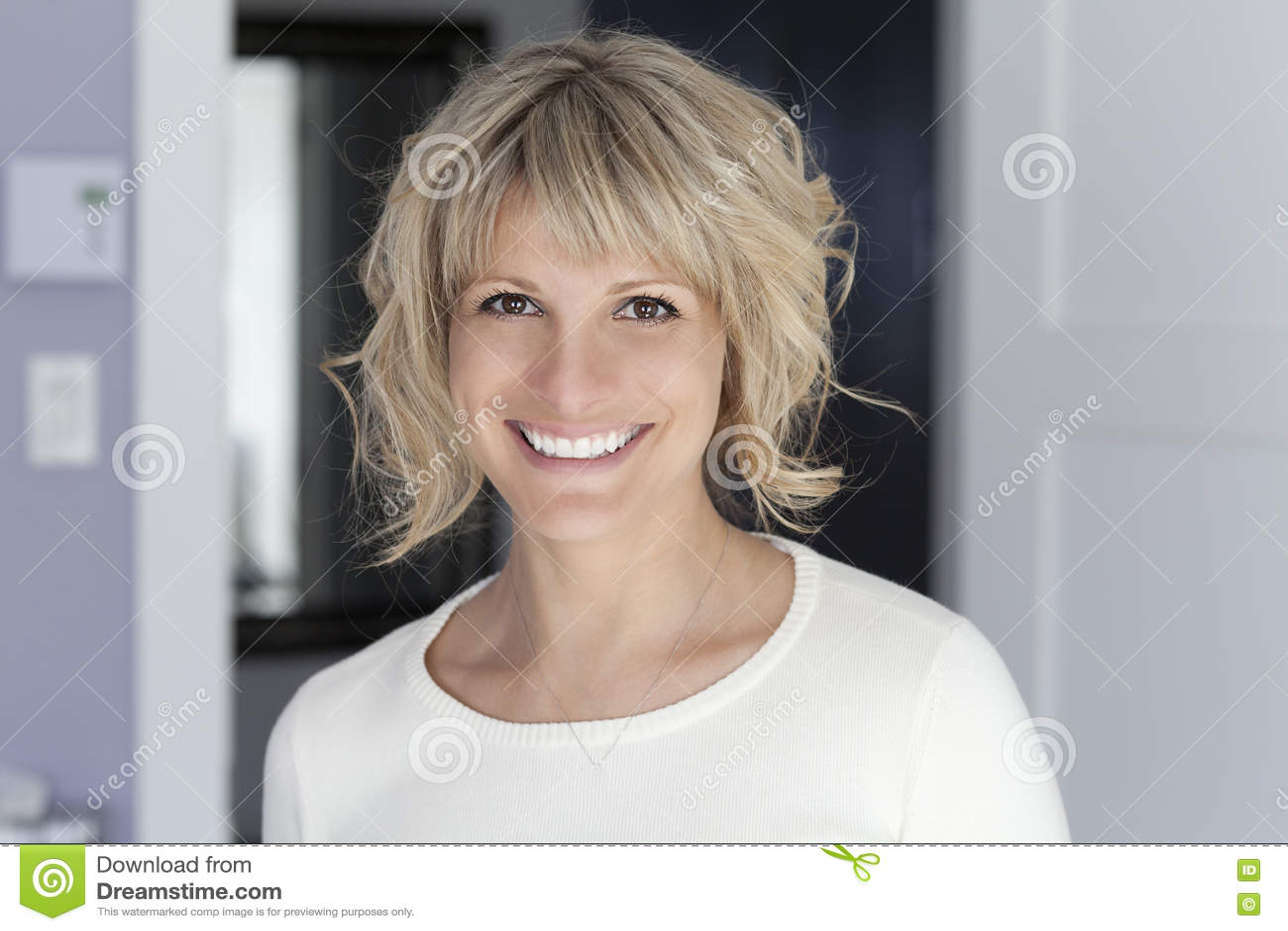 Stående av en mogen kvinna som ler på kameran