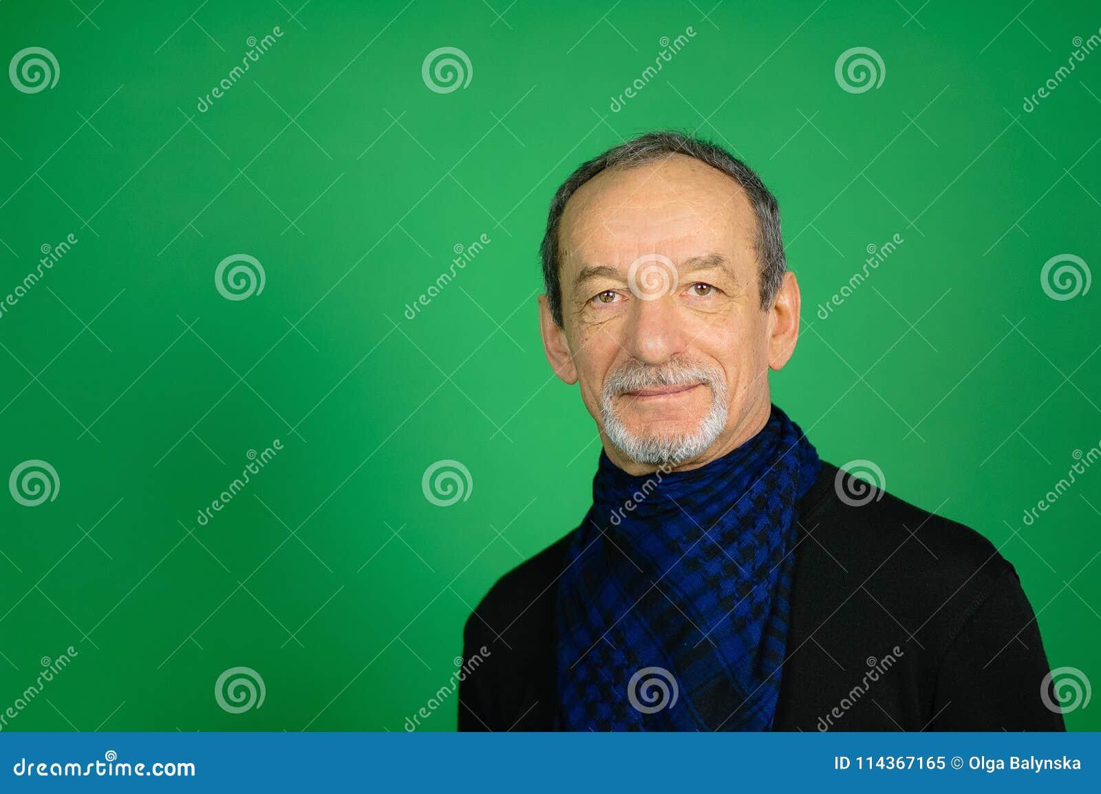 Stående av en mogen man på en grön bakgrund Svart tröja, blå halsduk runt om hans hals, välvilligt ansiktsuttryck