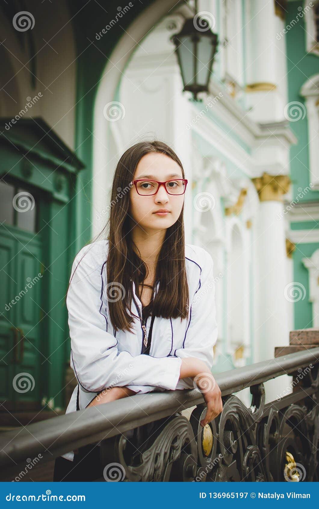 Stående av en nätt ung flicka med exponeringsglas på bakgrunden av en härlig gammal byggnad