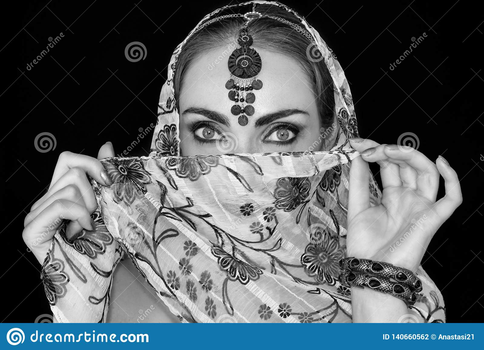 Stående av en orientalisk ung kvinna i en halsduk med en prydnad och juvlar i svartvitt