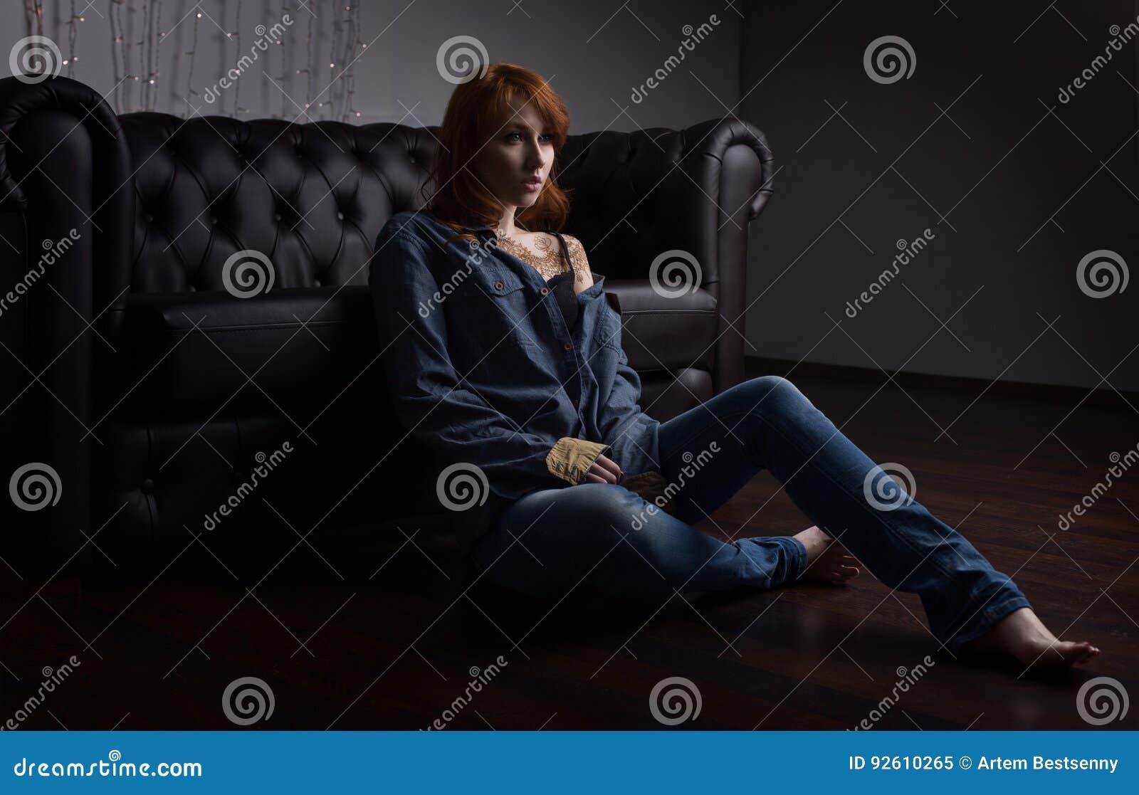 Stående av en rödhårig flicka i jeans skjorta och jeans som sitter på den svarta soffan på golvet