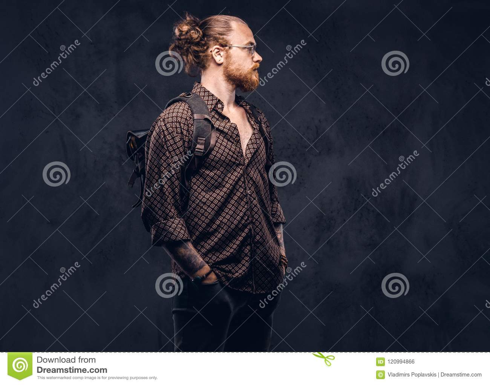Stående av en rödhårig manhipsterstudent i iklädda exponeringsglas en brun skjorta, håll en ryggsäck som poserar på en studio