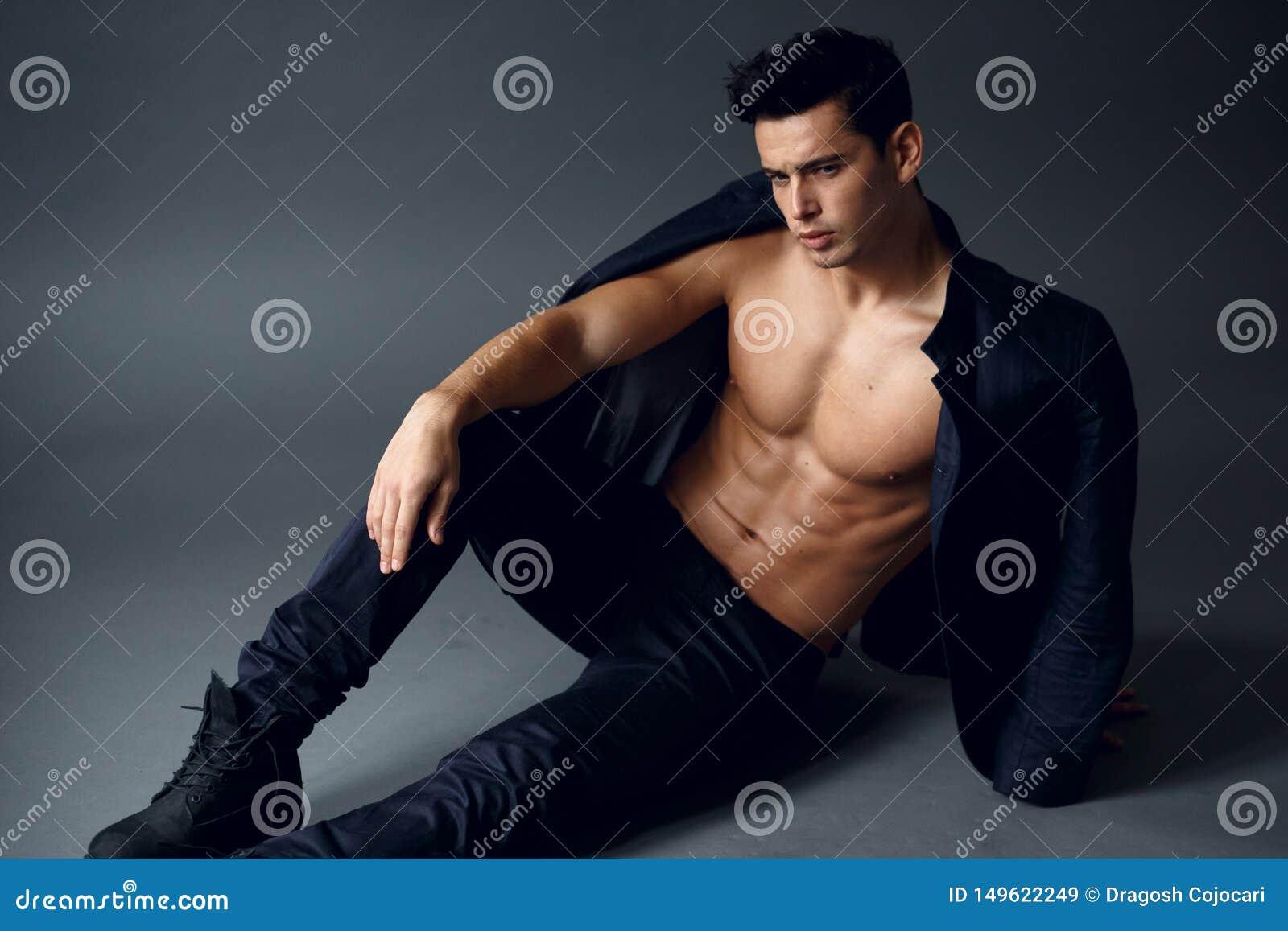 St?ende av en s?ker sexig ung man, med den nakna torson med omslaget p? hans skuldror som isoleras p? gr? bakgrund