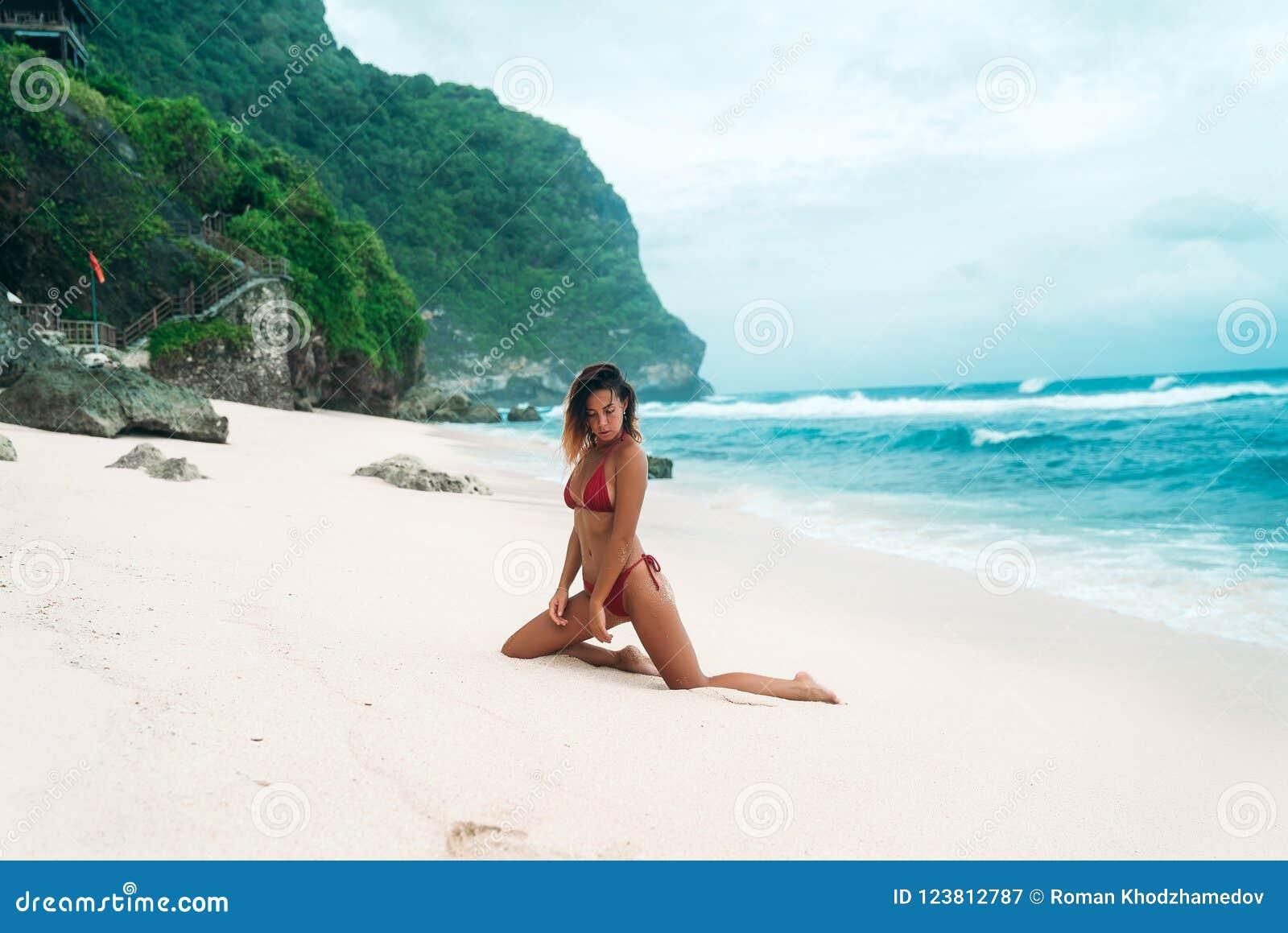 Stående av en sexig brunbränd flicka på stranden En ursnygg modell med ett åtstramande sportdiagram i en röd bikini