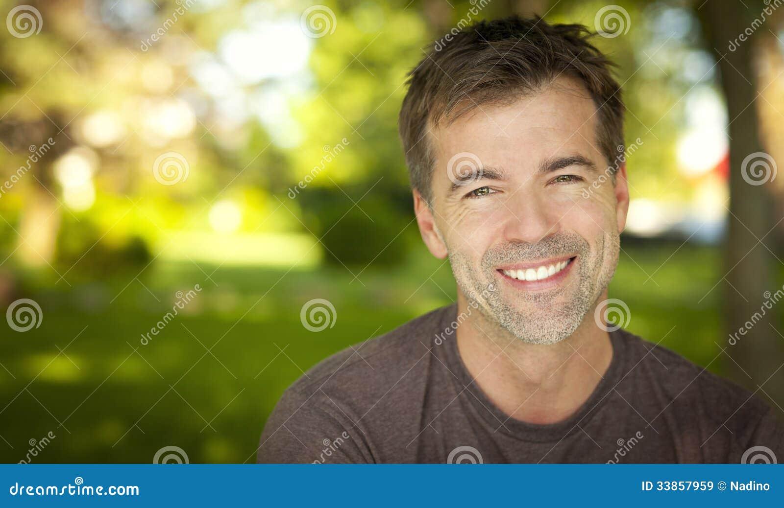 Stående av en stilig man som ler på kameran