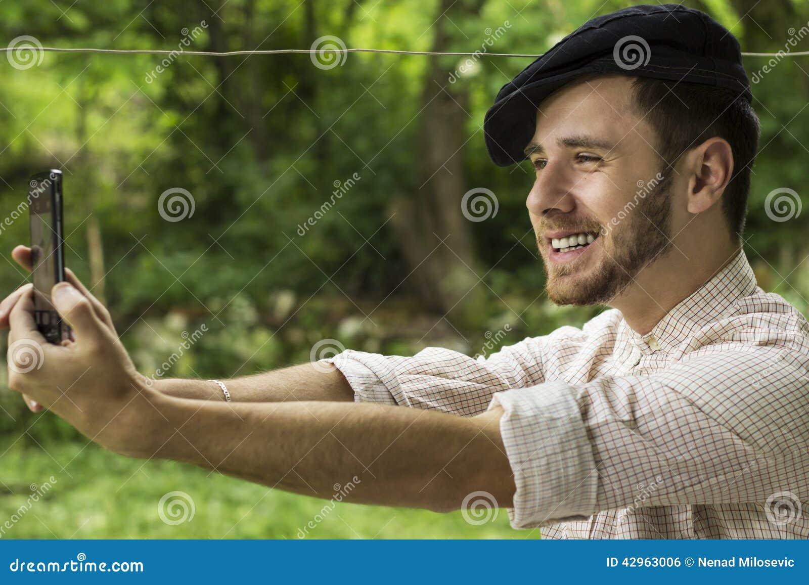 Stående av en stilig ung man med locket som tar selfietelefonen