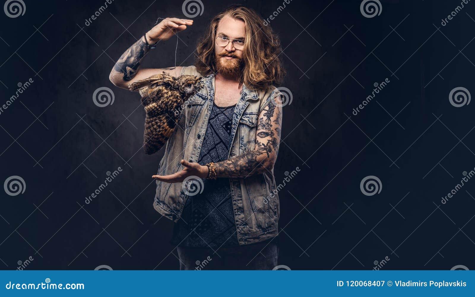 Stående av en tattoed rödhårig manhipsterman med långt det iklädda frodigt hår och fulla skägget enskjorta och omslagshåll