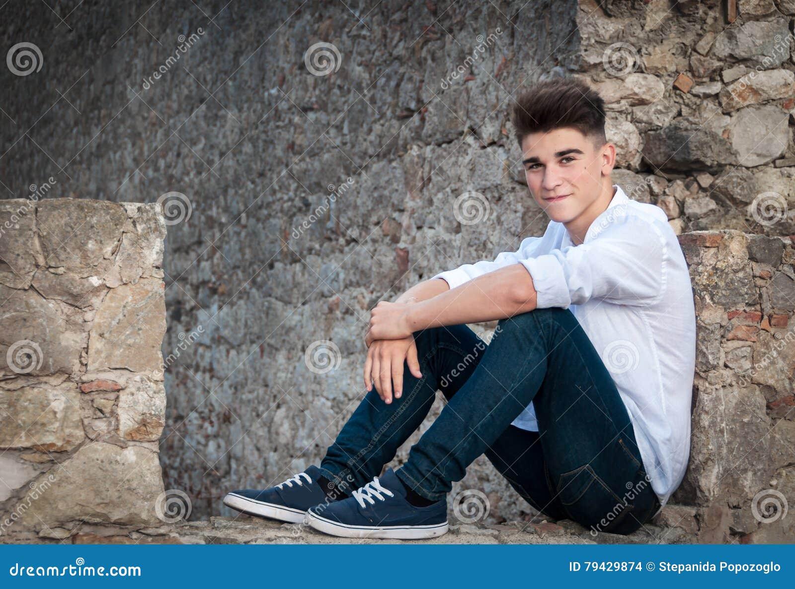 Stående av en tonåring Han sitter i en stenvägg dramatiskt