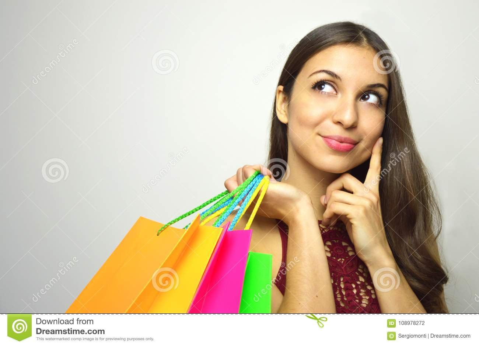 Stående av en trendig ursnygg brunett med påseshopparen i hennes hand som tänker vad för att köpa och ser till sidan kopieringssp