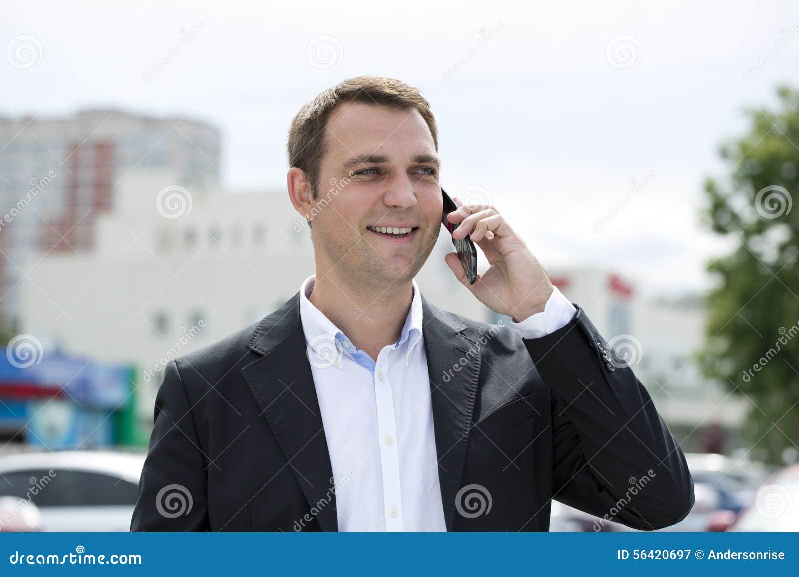 Stående av en ung affärsman i en mörk dräkt- och vitskjorta