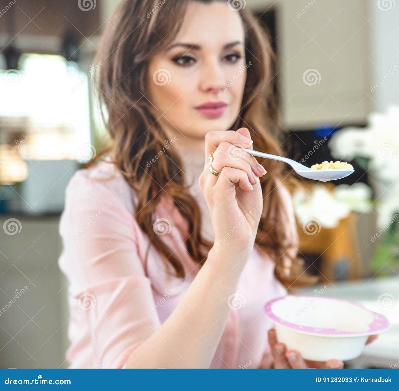 Stående av en ung dam som matar en behandla som ett barn