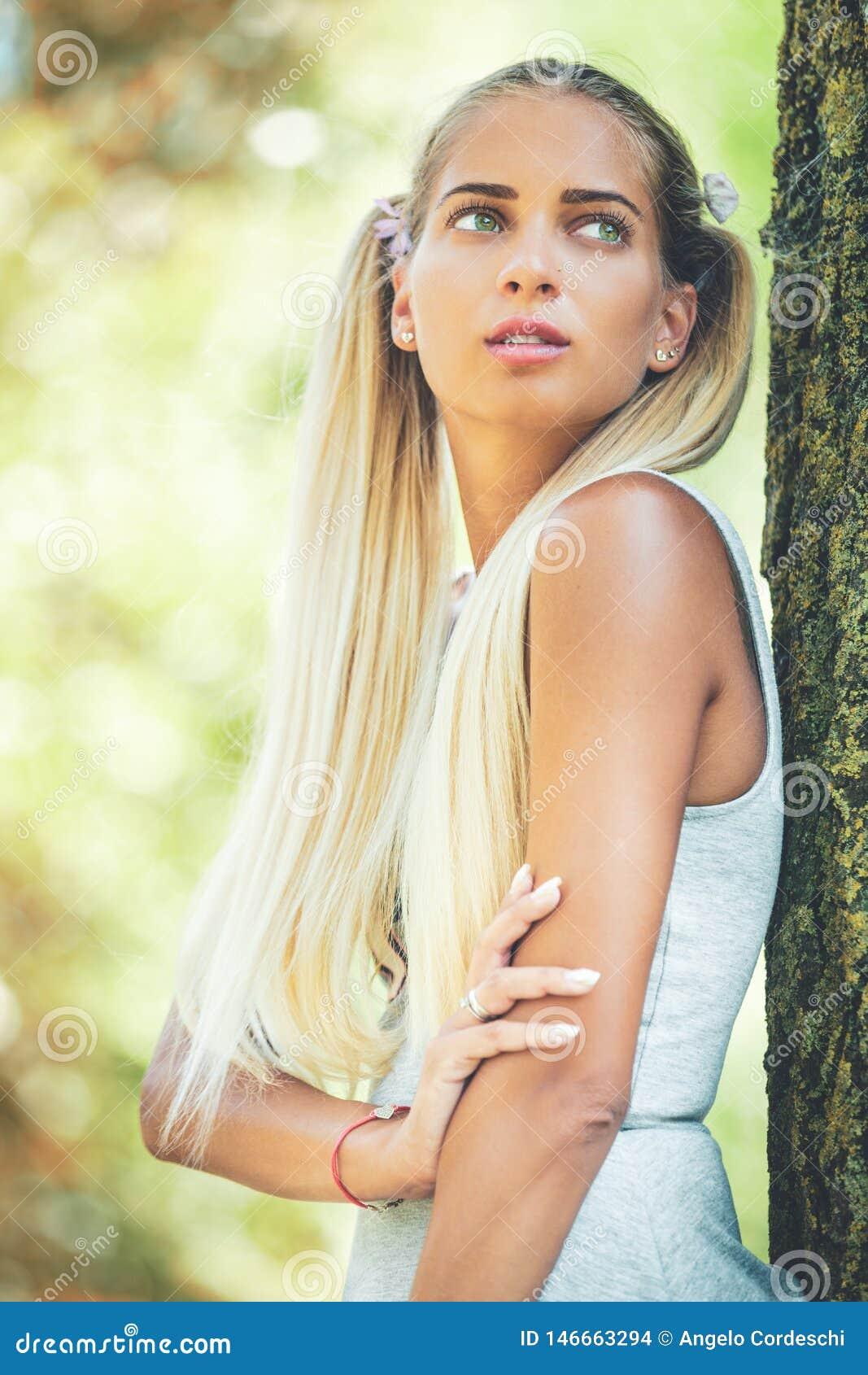Stående av en ung drömmarekvinna i naturen Långt blont hår, gröna ögon