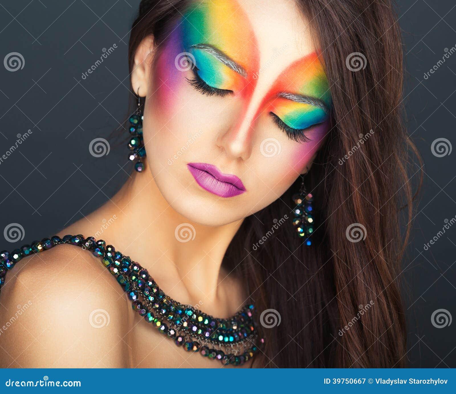 Stående av en ung härlig flicka med en ljus multico för mode
