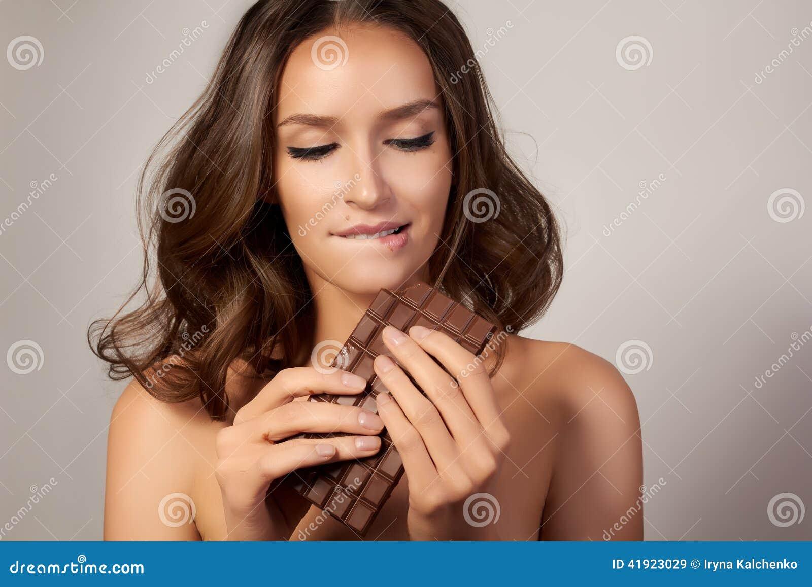 Stående av en ung härlig flicka med mörkt lockigt hår, kala skuldror och halsen som rymmer en chokladstång för att tycka om smake