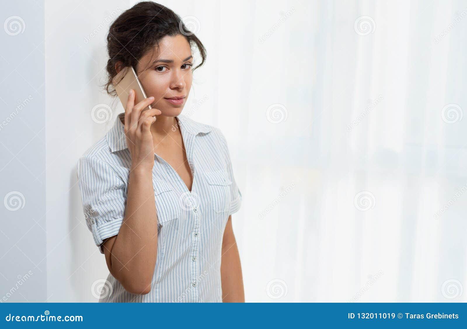 Stående av en ung härlig kvinna med en telefon