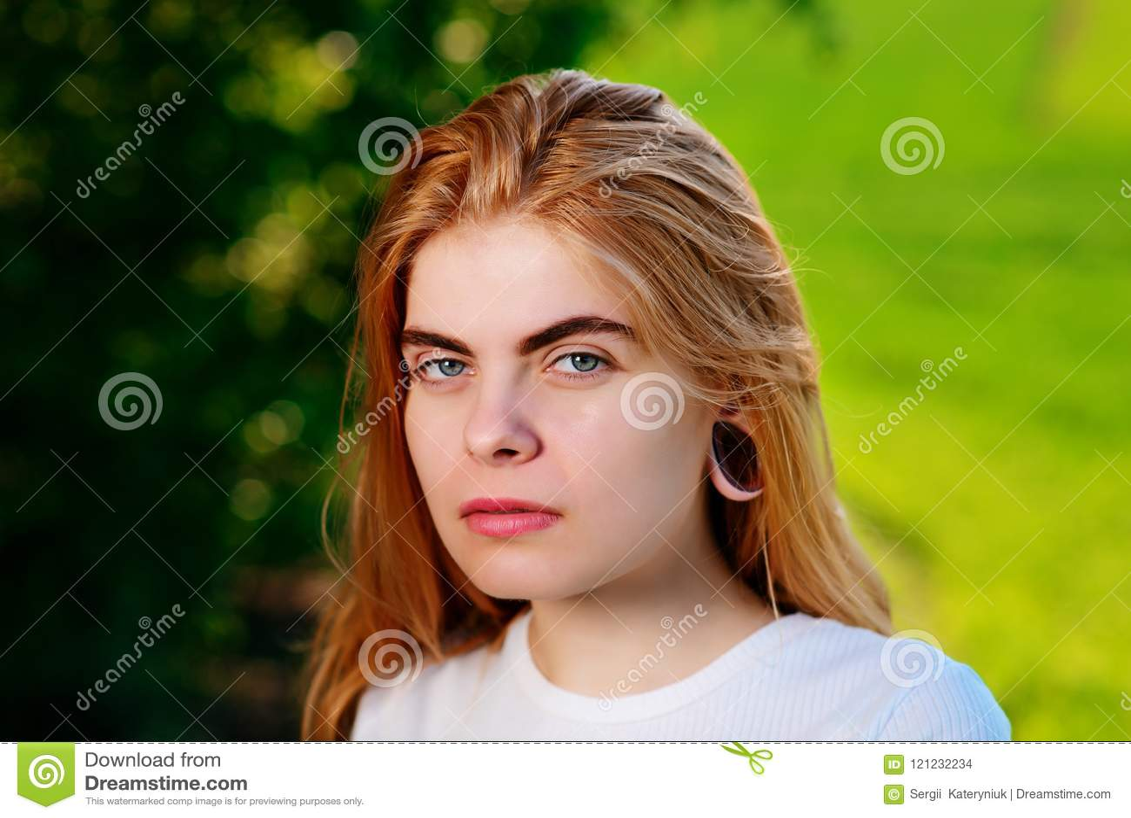 Stående av en ung härlig kvinna med trätunneler i hennes e