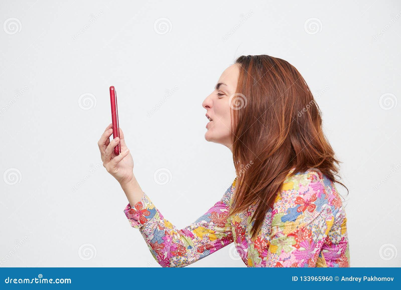 Stående av en ung kvinna i färgskjorta som skriker på en mobiltelefon som isoleras på en vit bakgrund hårfärg är brun