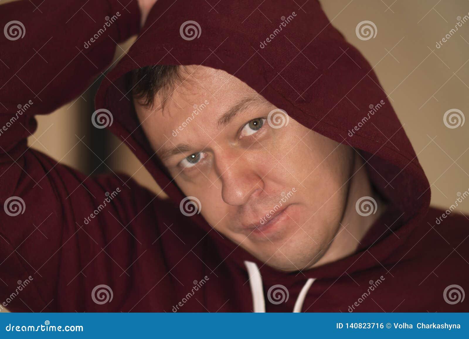 Stående av en ung man i en huv som ser kameran, närbild