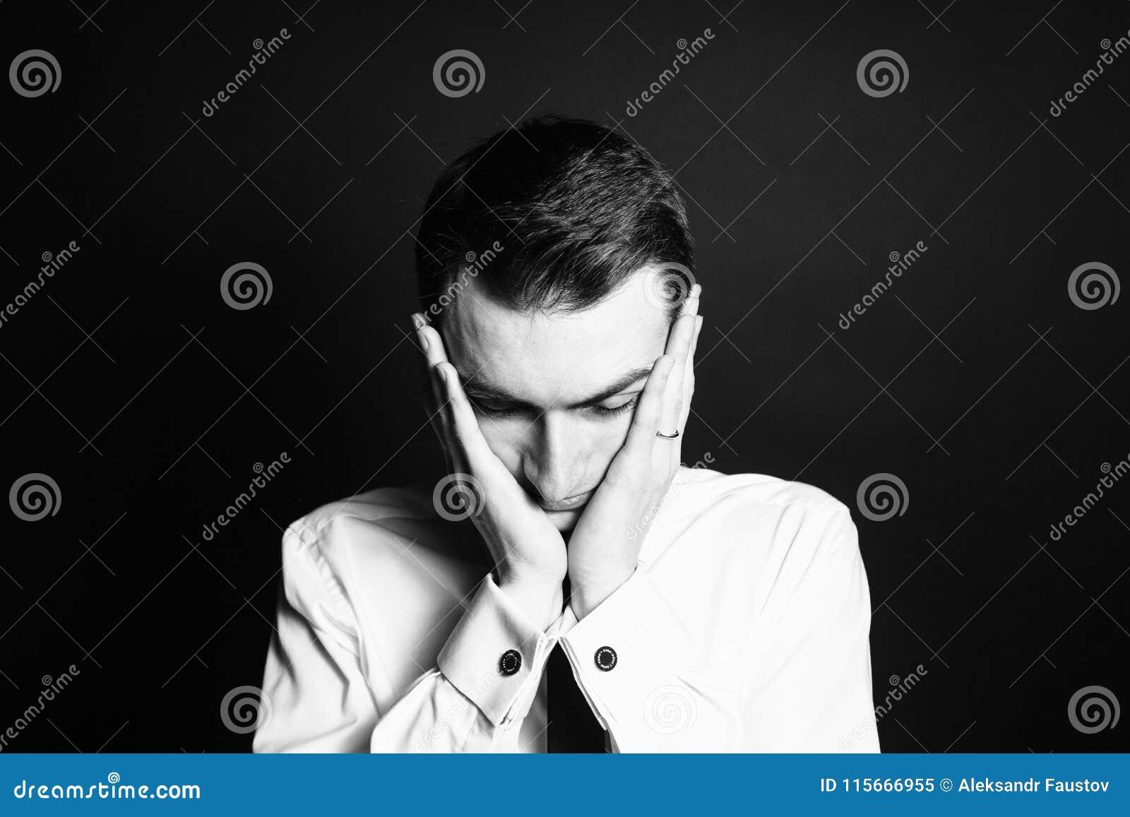 Stående av en ung man i en vit skjorta, händer på huvudet
