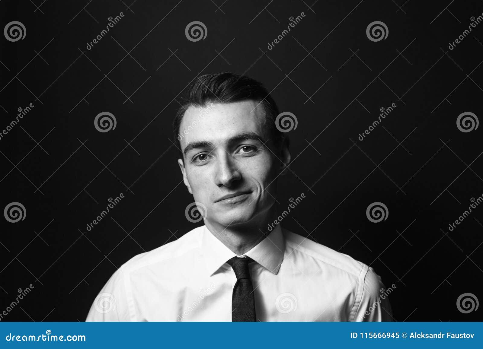 Stående av en ung man i en vit skjorta och smoking