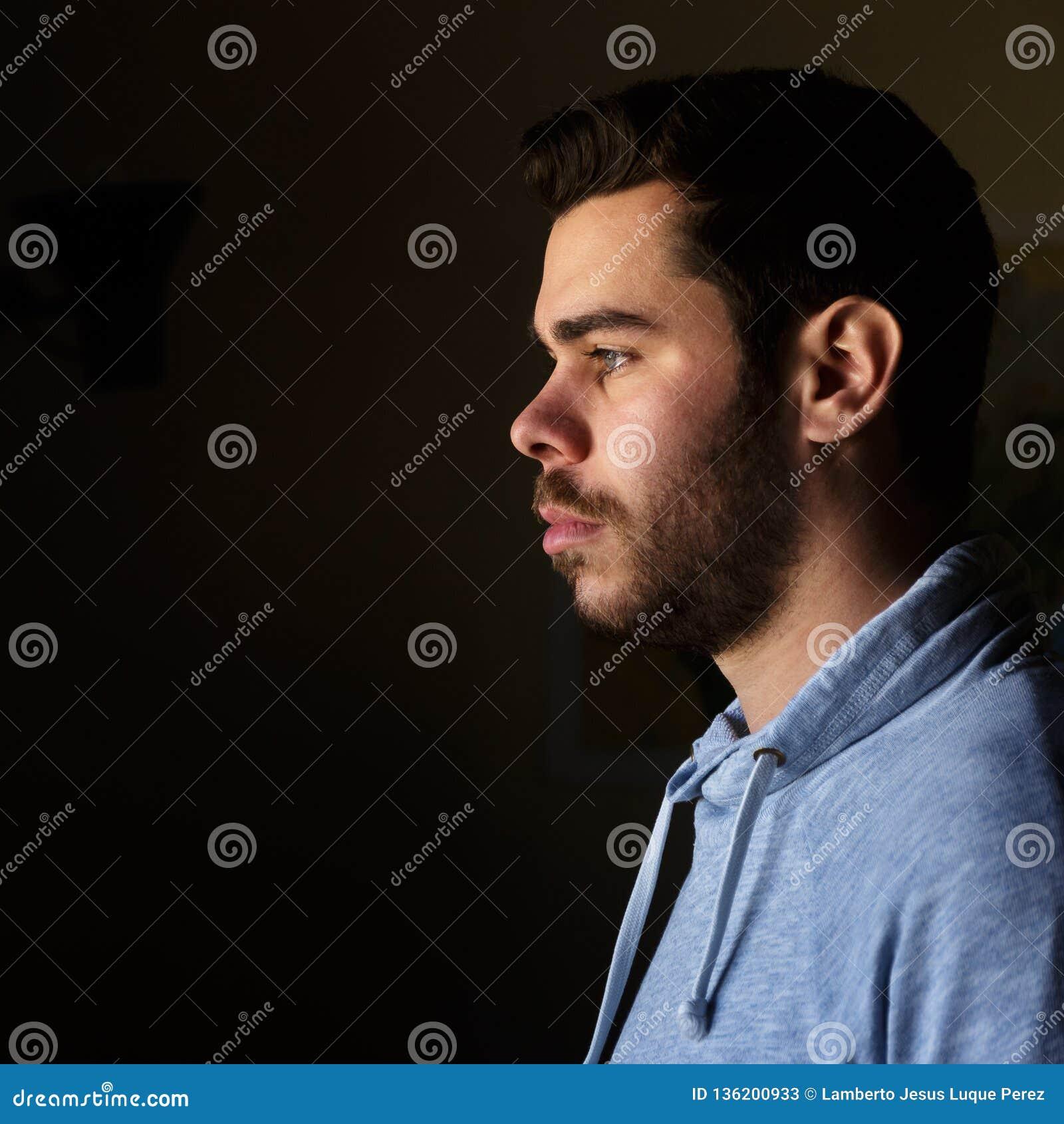 Stående av en ung man med ett skägg i profil