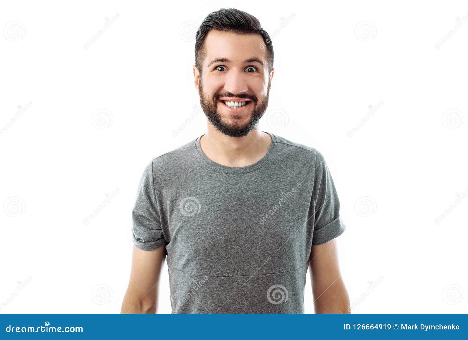 Stående av en ung man med ett skägg som bär en grå skjorta som poserar för kameran med ett stort leende på en vit bakgrund