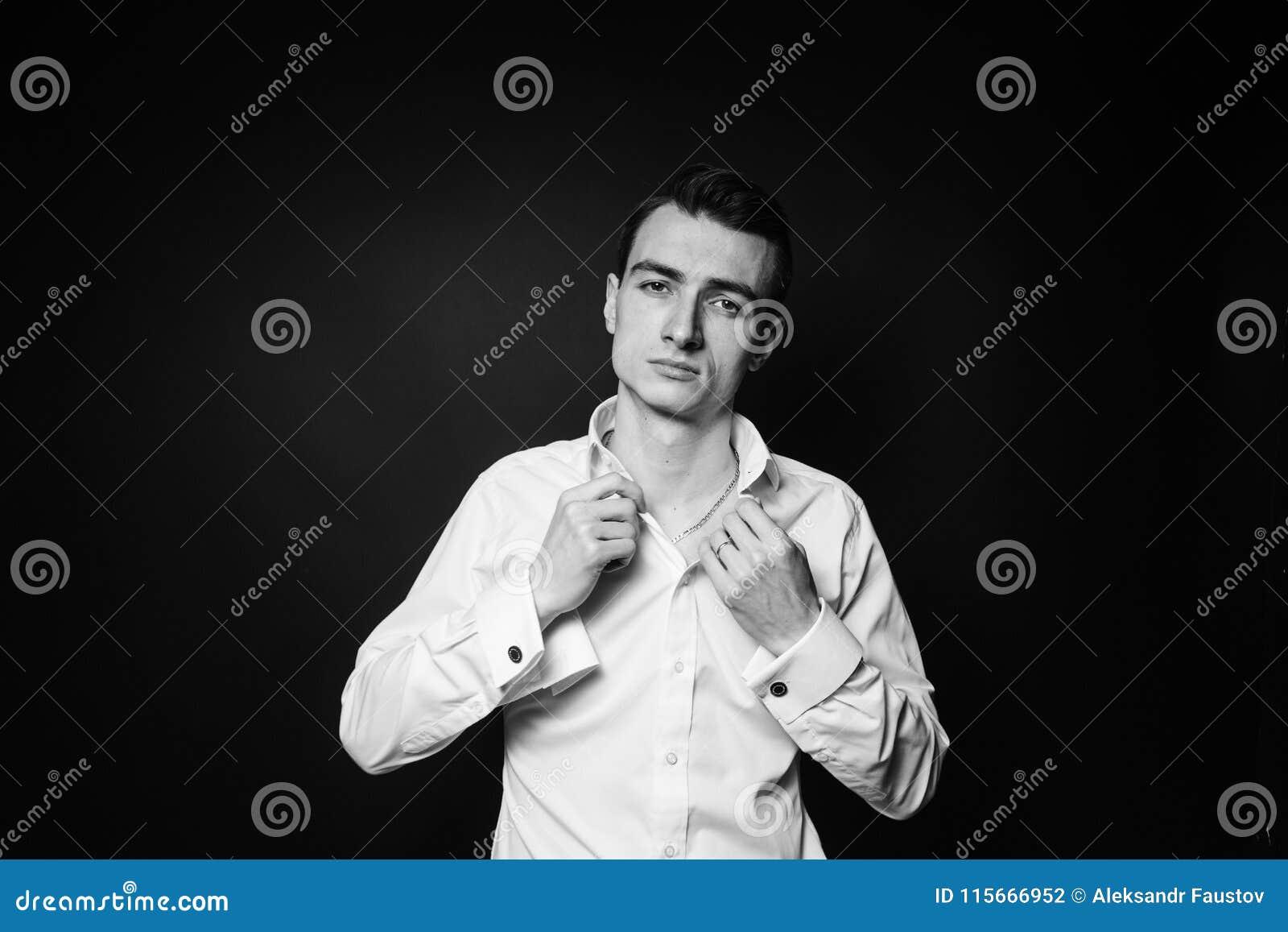Stående av en ung man som knäpper upp den vita skjortan