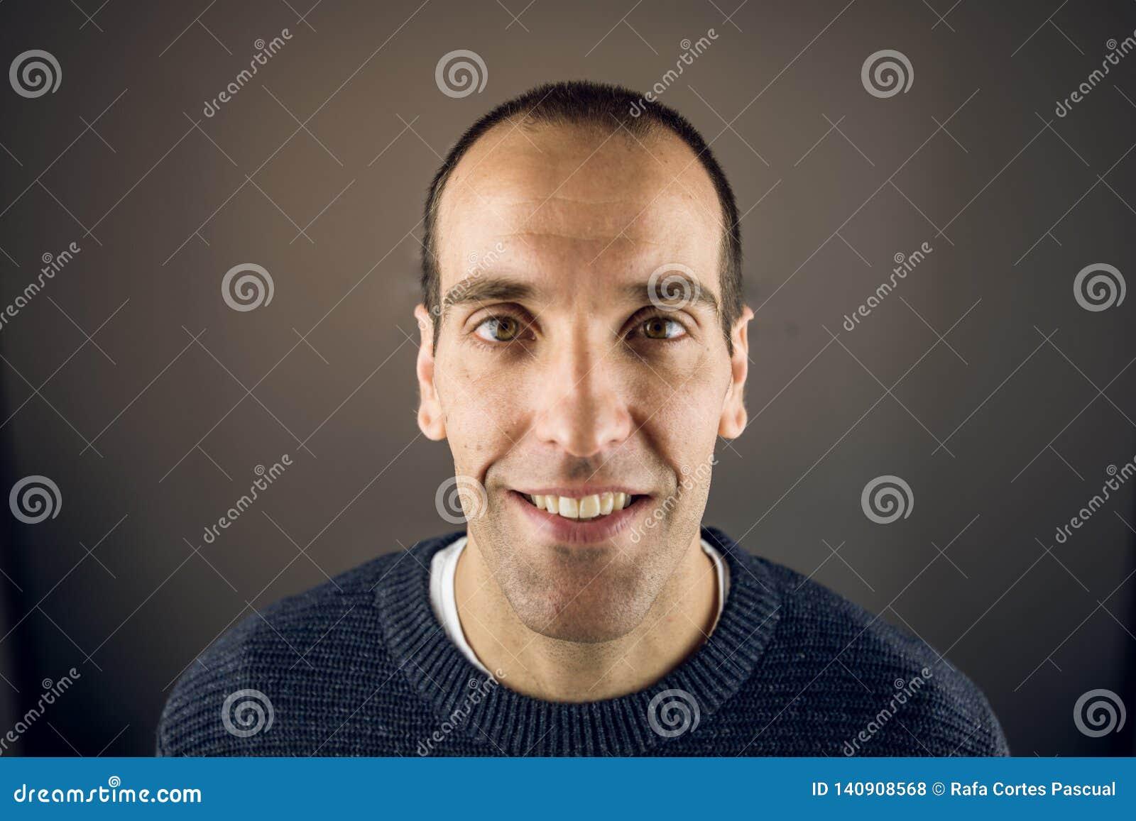 Stående av en ung man som ser kameran med lyckligt uttryck och att le