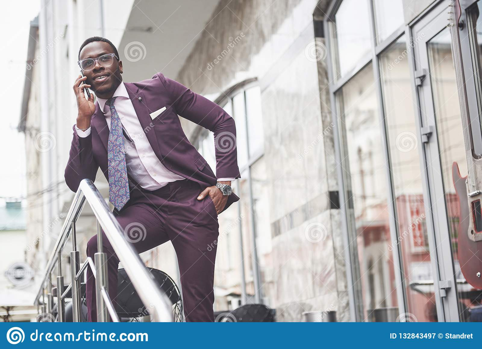 Stående av en ung och stilig afrikansk amerikanaffärsman som talar i en dräkt över telefonen Förbereda sig för en affär