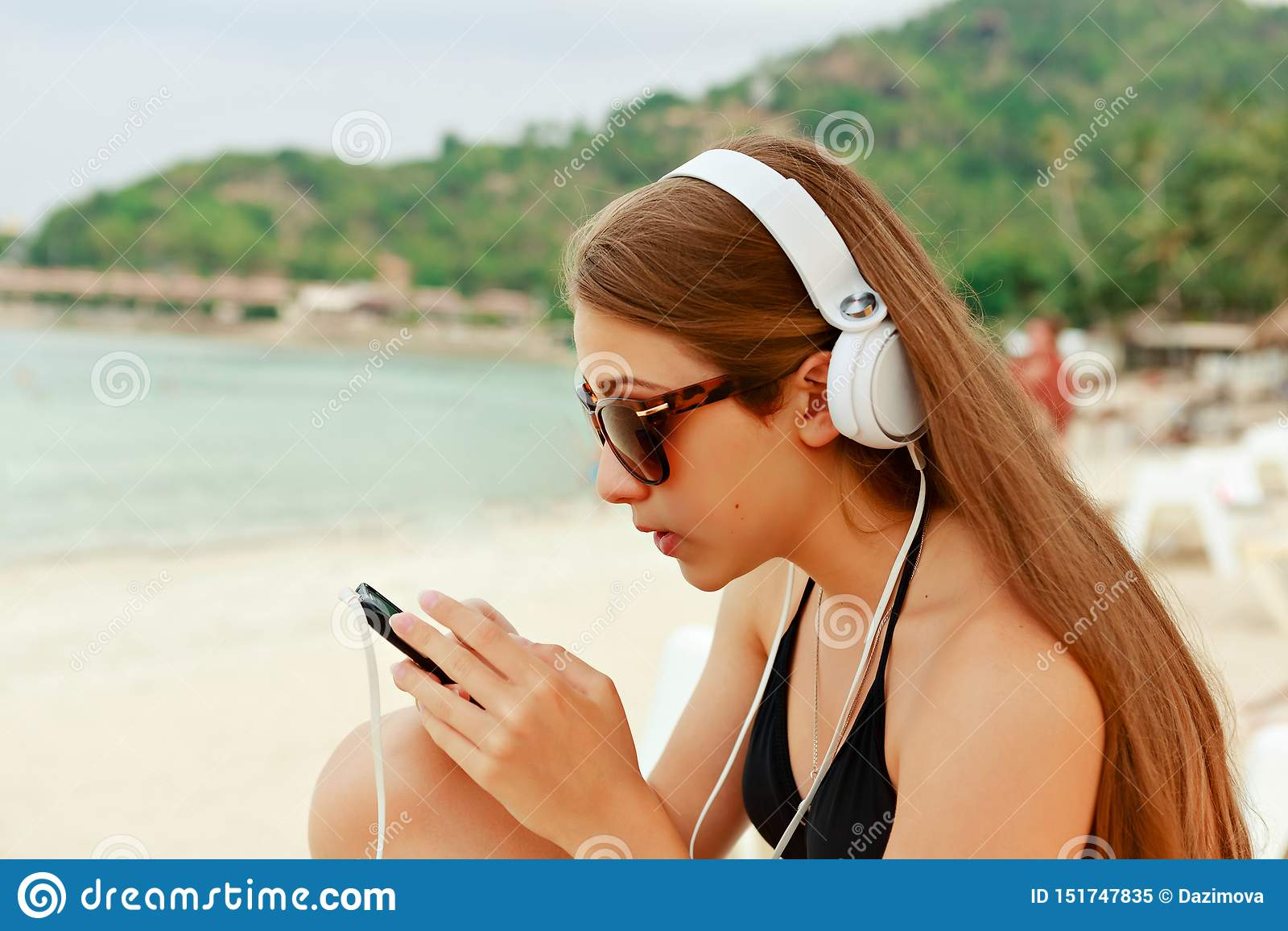 Stående av en ung skönhettonåringflicka som sitter av den vita sandstranden som lyssnar till musik genom att använda hörlurar och