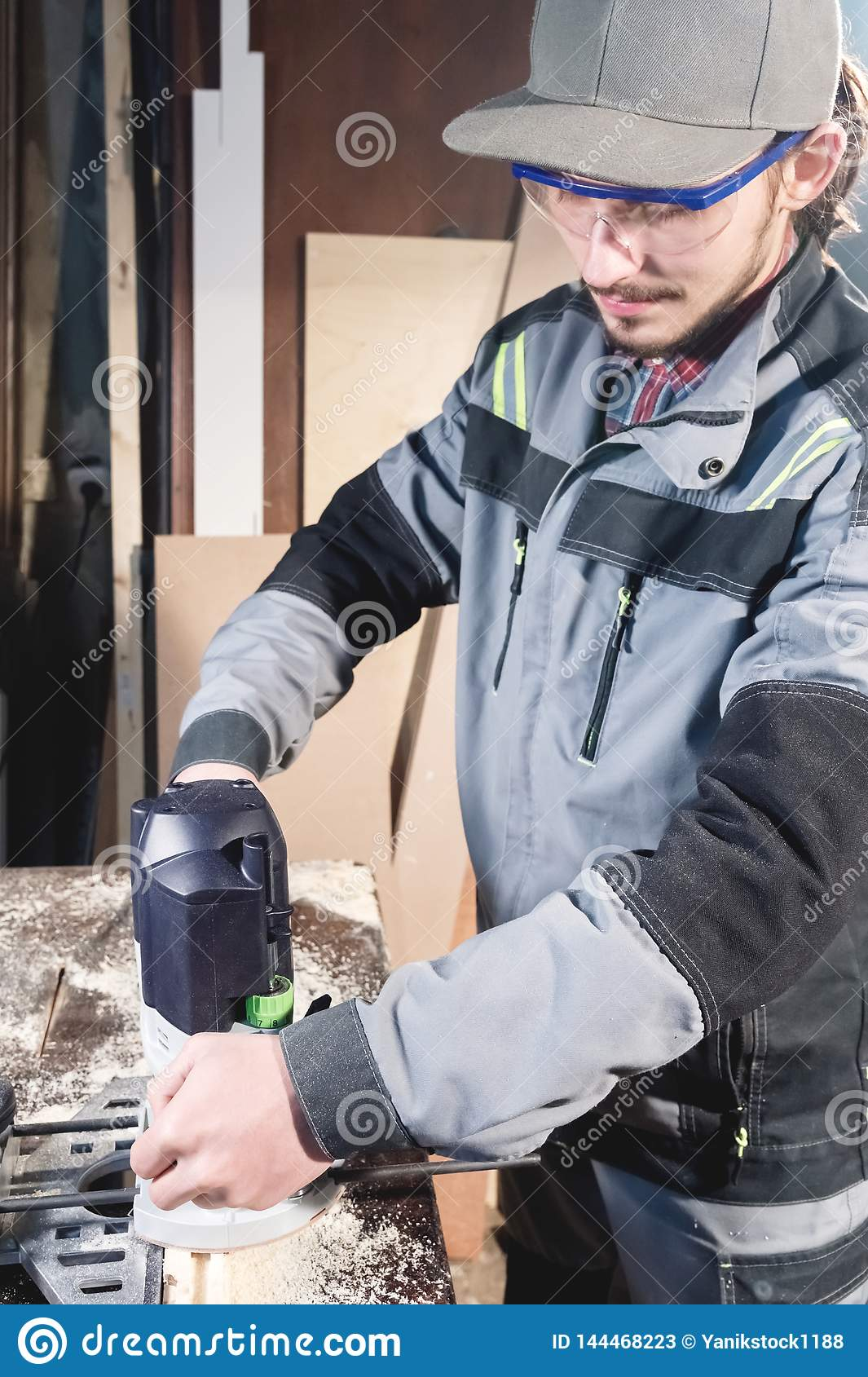 Stående av en ung snickareföreningsmänniska med den elektriska mala skäraren i händerna av en arbetare i ett hem- seminarium star