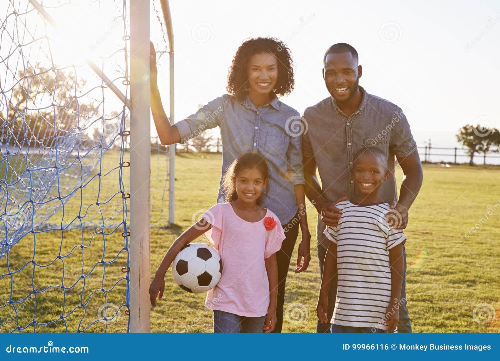 Stående av en ung svart familj under en fotbolllek