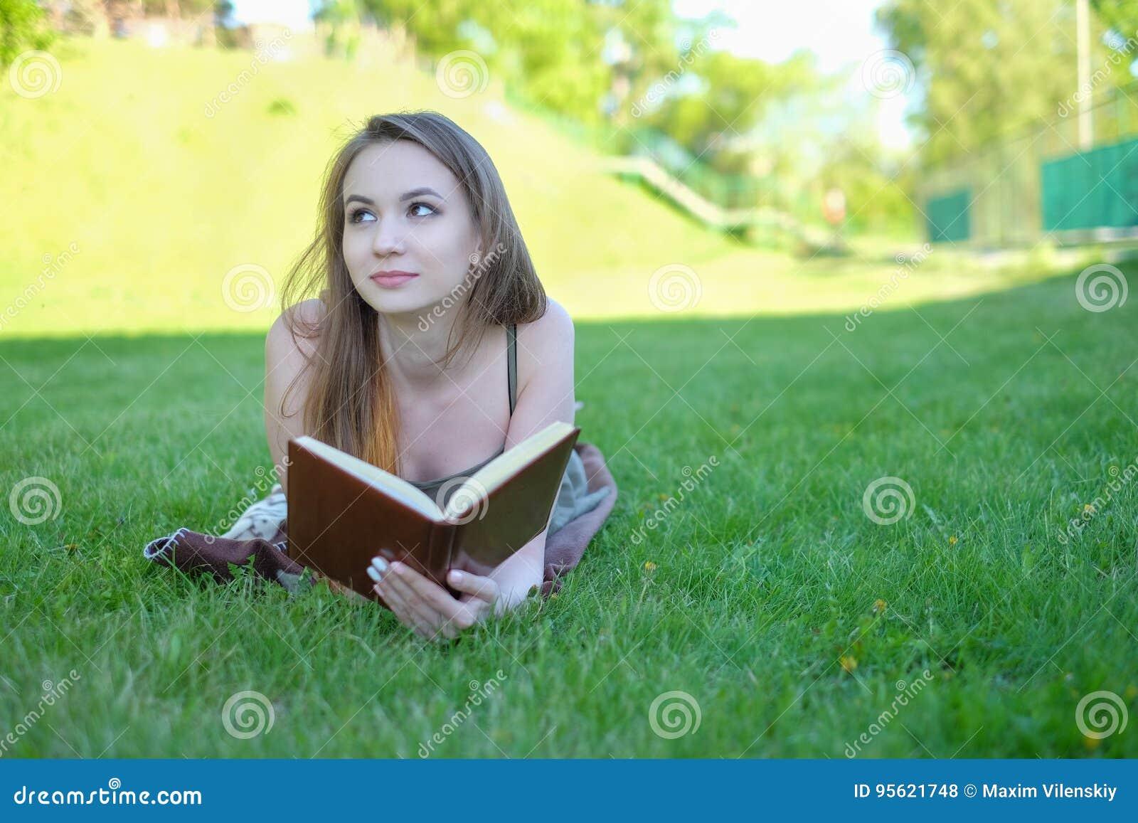 Stående av en ursnygg ung läsebok för brunettstudent utomhus
