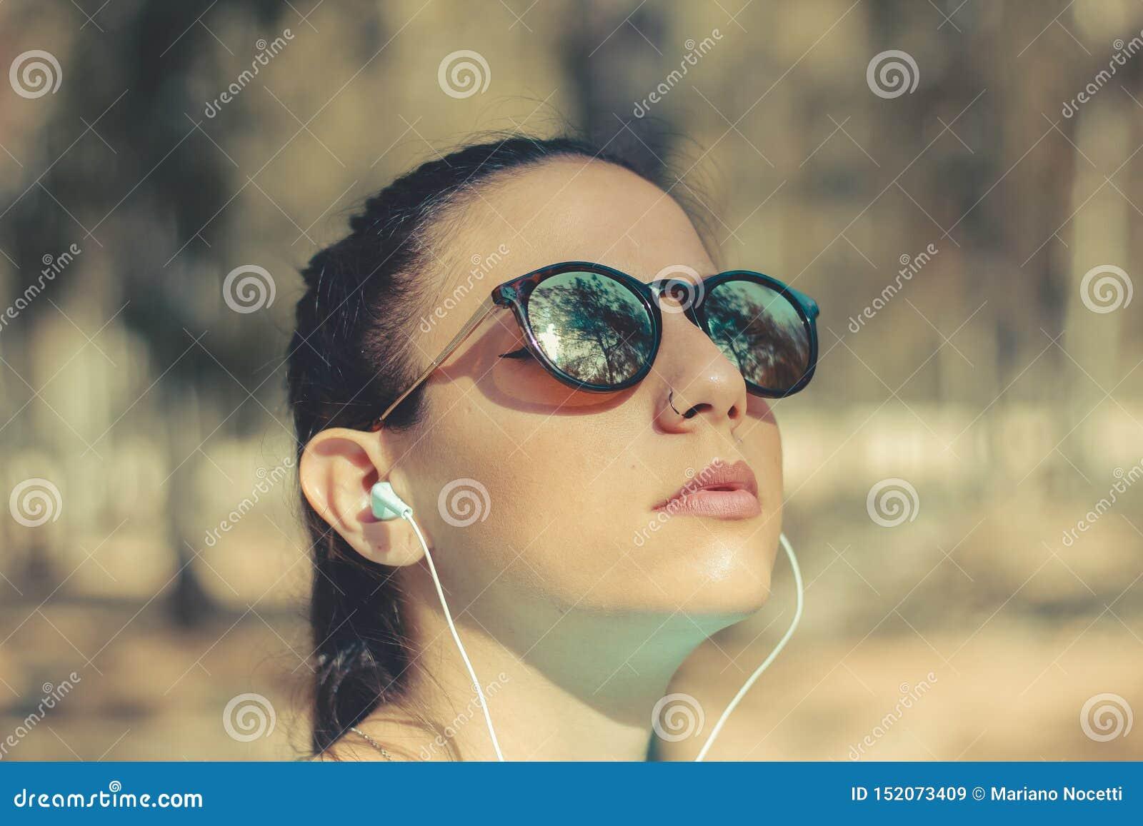 Stående av en utomhus- lyssnande musik för ung flicka