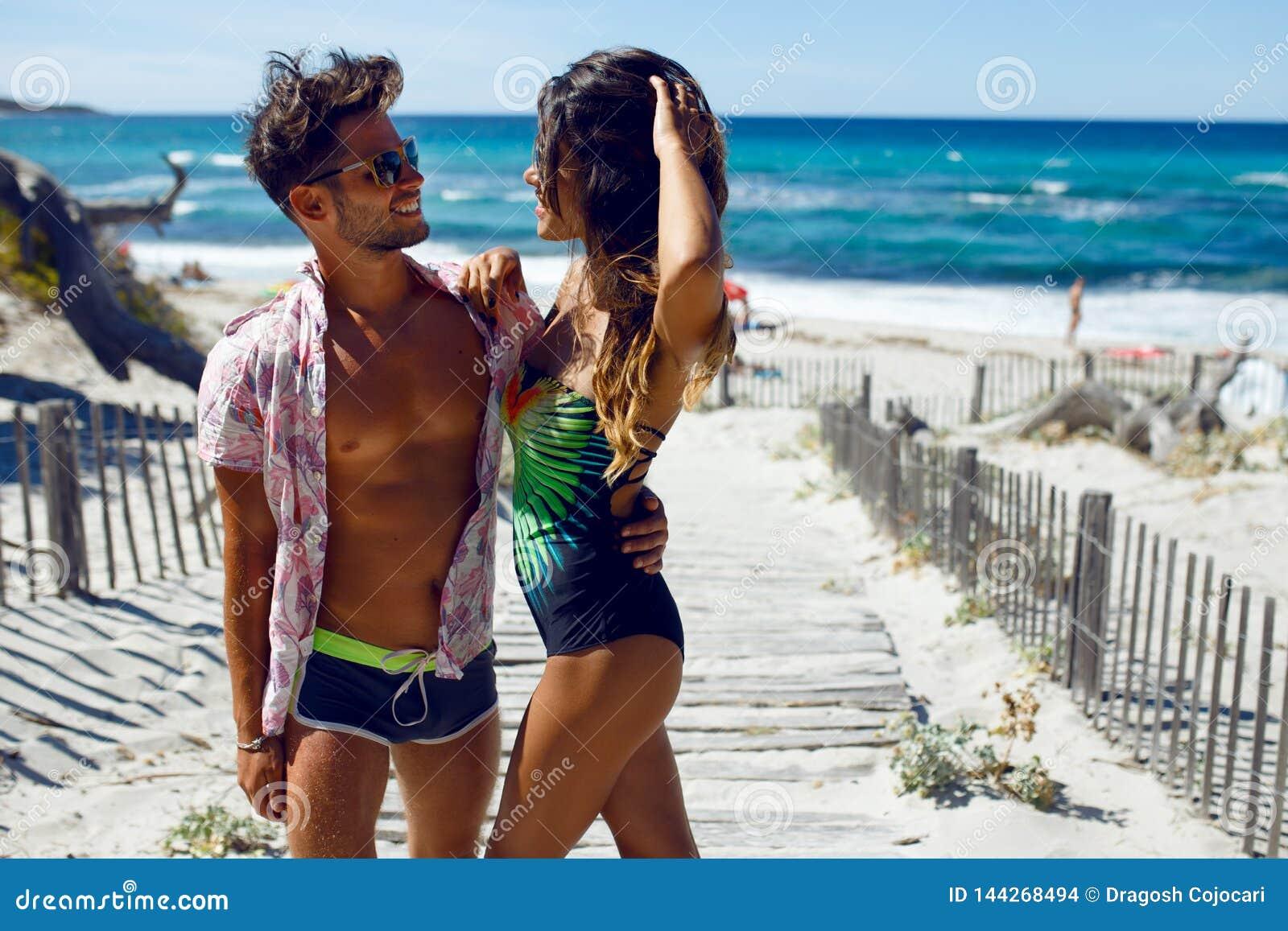 Stående av ett attraktivt, posera för lyckapar som är sexigt på stranden på den Korsika ön, på seascapebakgrund