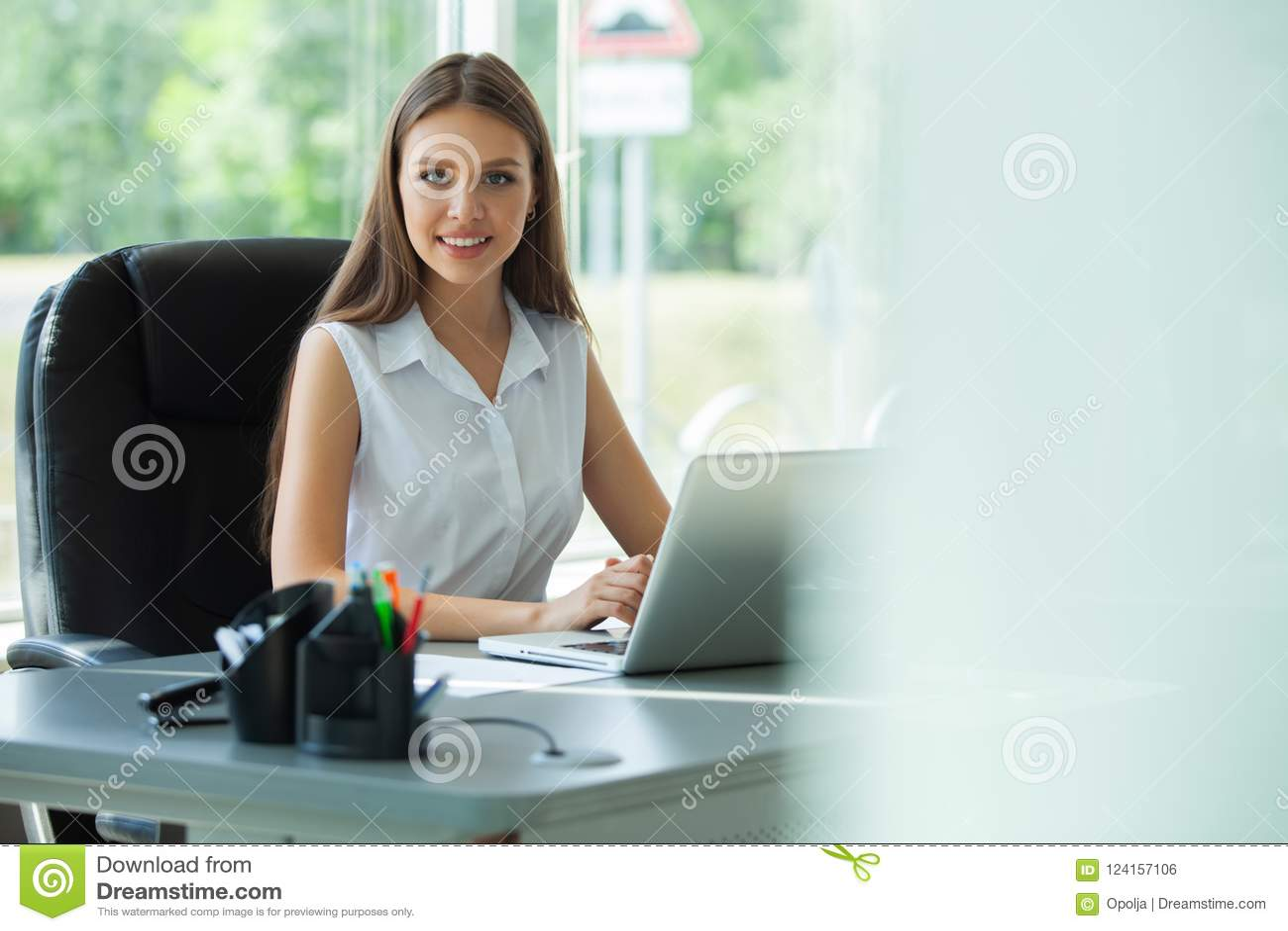 Stående av ett gladlynt affärskvinnasammanträde på tabellen i regeringsställning och se kameran