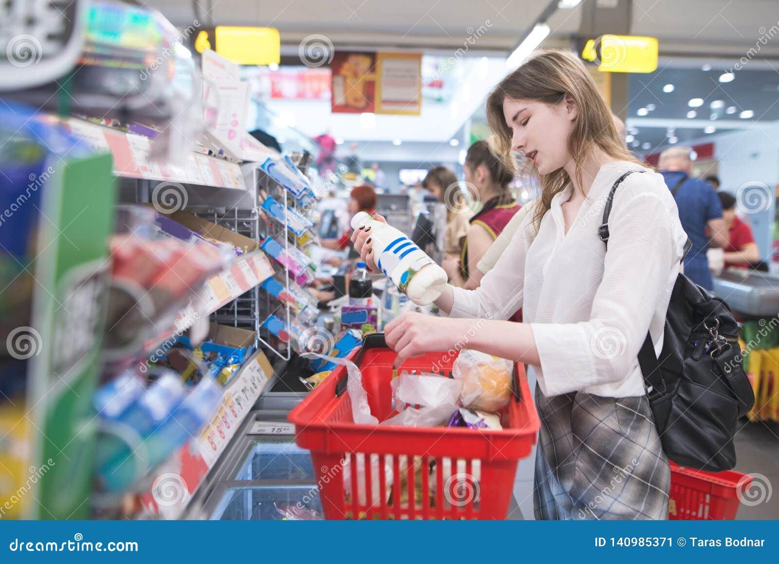 Stående av ett härligt kvinnaanseende i linje på supermarkets kassörska och att dra ut den röda korgen