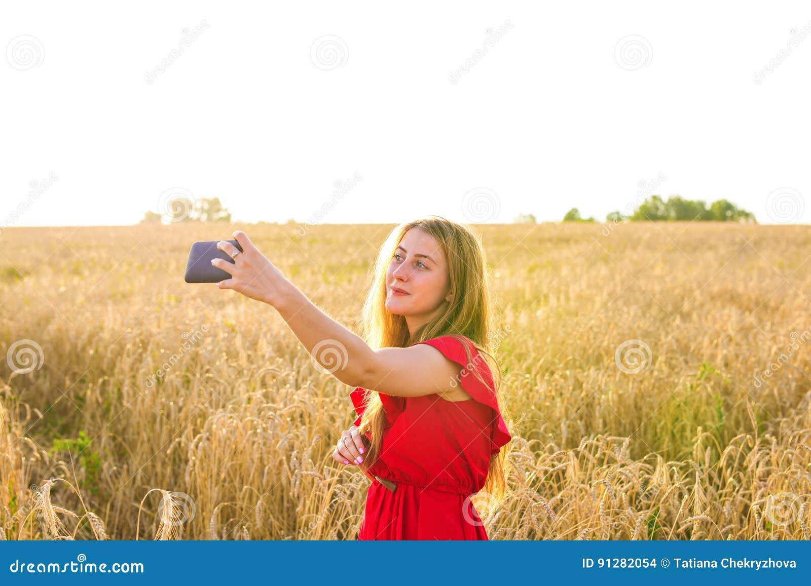 Stående av ett le foto för ung flickadanandeselfie i fältet