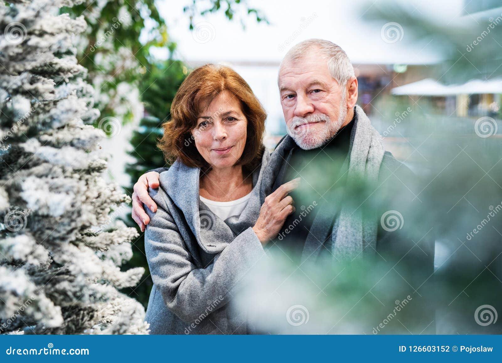 Stående av ett lyckligt högt par som gör jul som tillsammans shoppar
