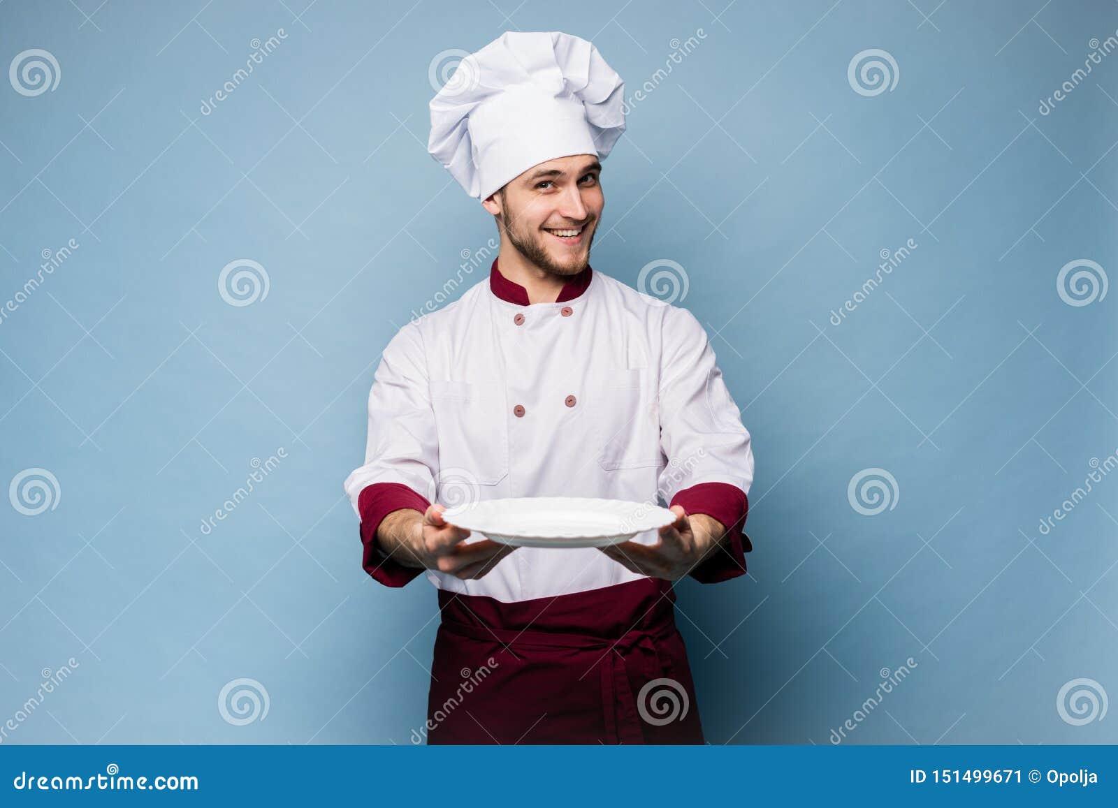Stående av ett lyckligt manligt kockkockanseende med plattan som isoleras på ljust - blå bakgrund